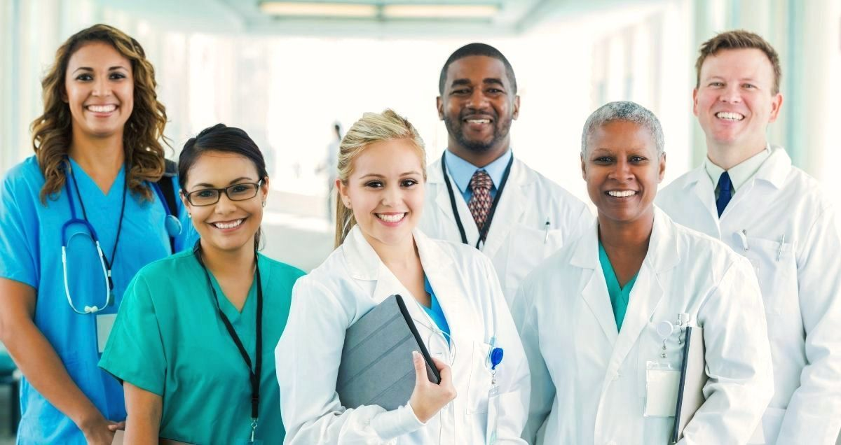 A diverse group of smiling doctors and nurses stand in a brightly lit hospital hallway.