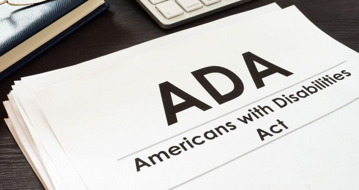 """A stack of papers with the """"Americans with Disabilities Act"""" written on it on a dark-wood desk with a calculator and a binder."""