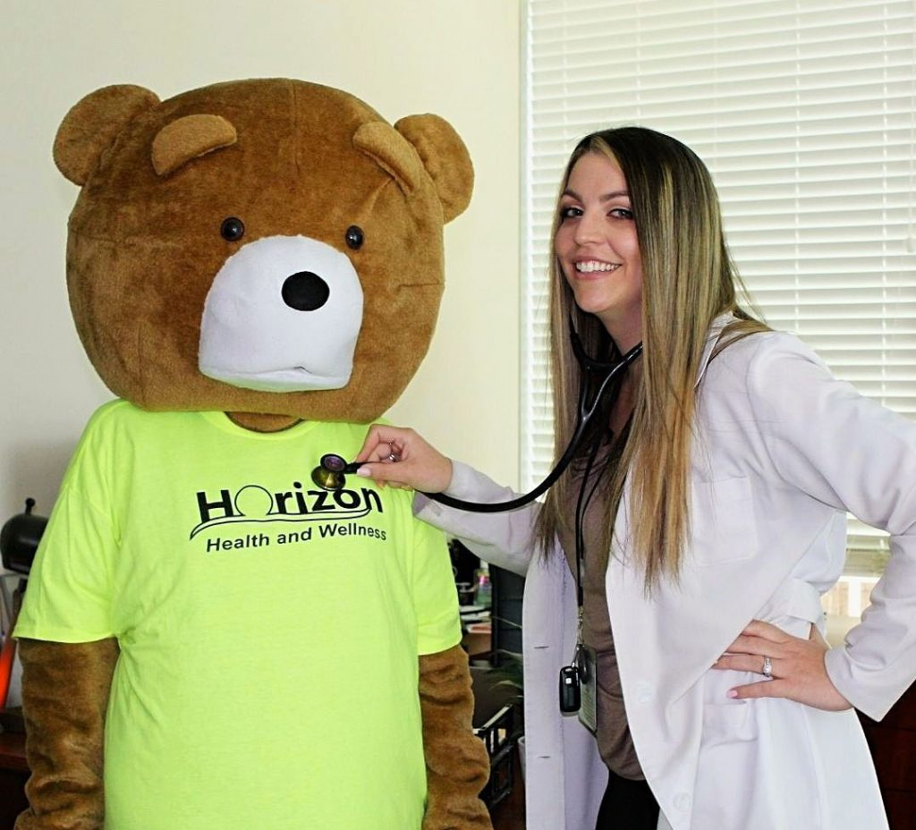 Cubby the Bear getting his heart checked by our doctor with a stethoscope.