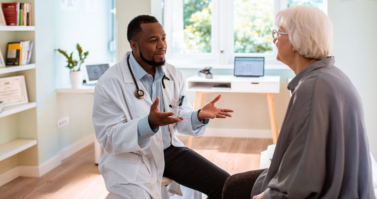 A Black doctor with a lab coat and stethoscope talking to an elderly Caucasian patient in his office.
