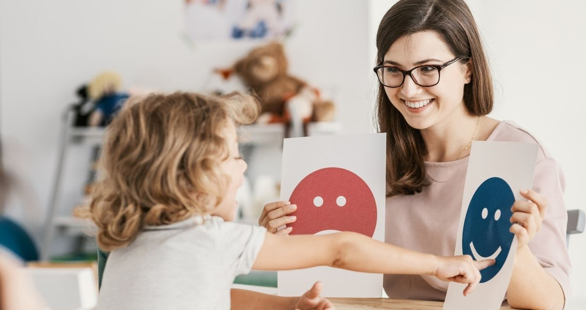 A child in a counseling session points to a sign with a smiling blue face that a therapist with glasses is holding.
