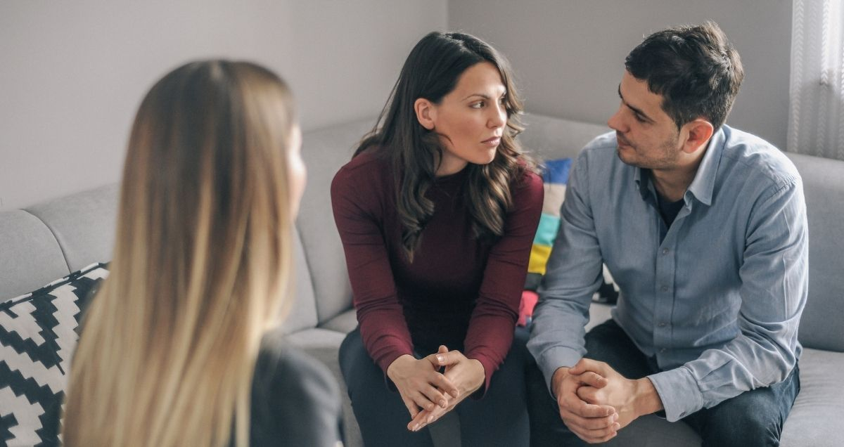 A tense marriage counseling session with a husband, wife, and therapist.