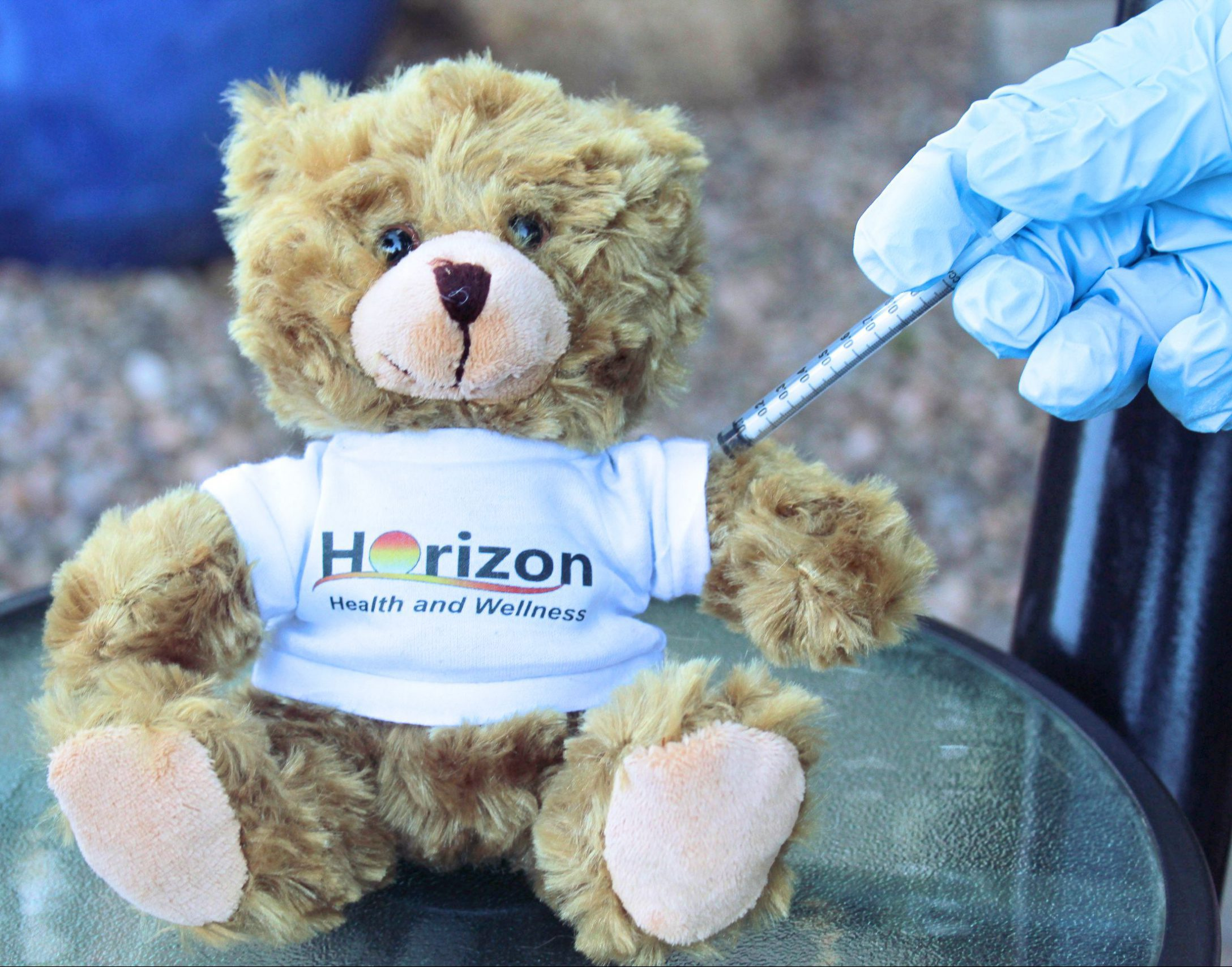 A hand with a glove giving a brown, stuffed bear wearing a Horizon Health and Wellness shirt the COVID vaccine in its arm.