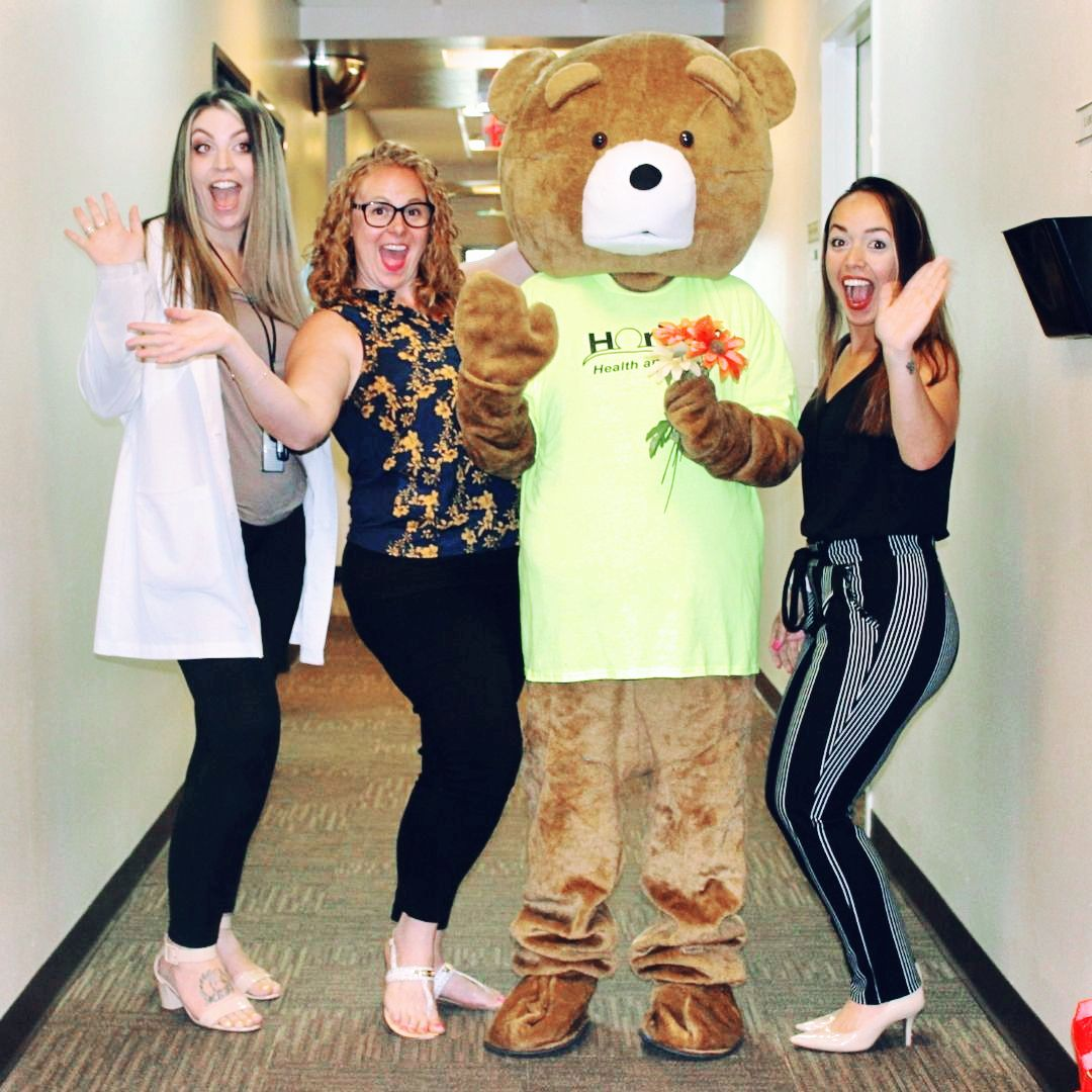 Cubby Bear with flowers and three happy staff members waving.