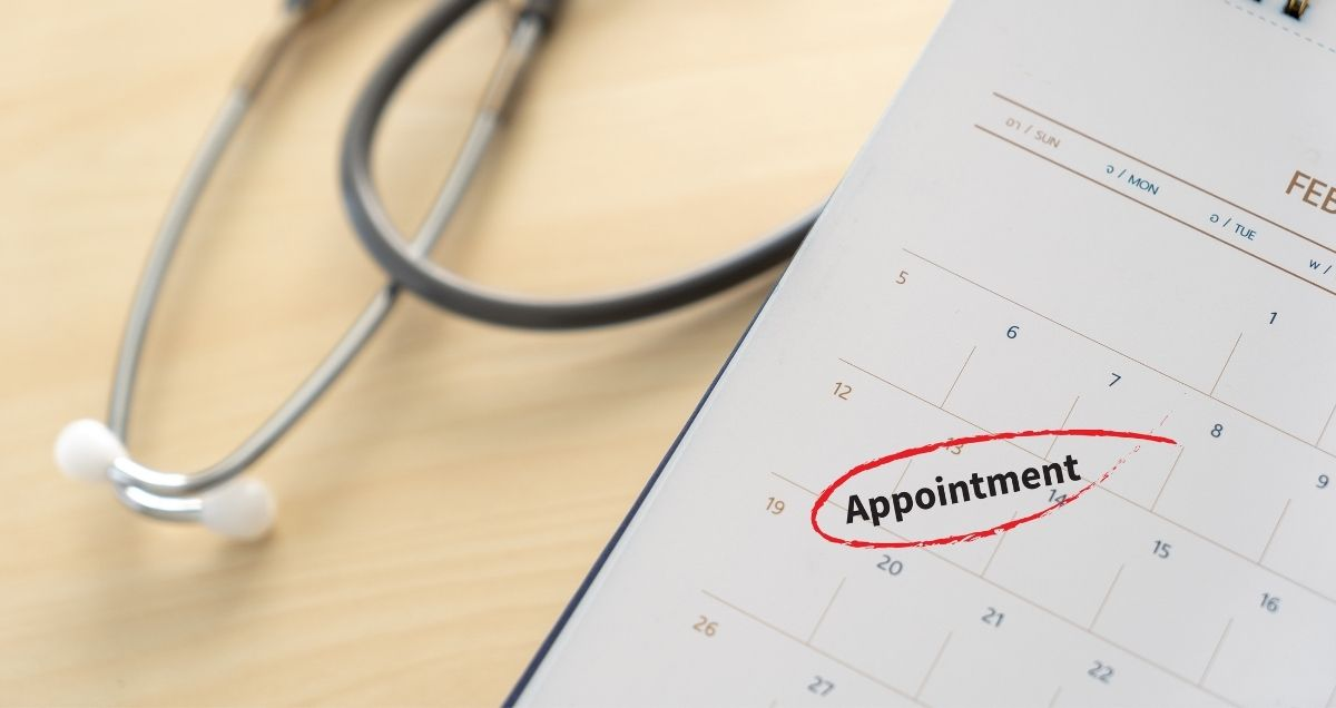 """A closeup of a stethoscope and a calendar with the word """"appointment"""" circled on it in red."""