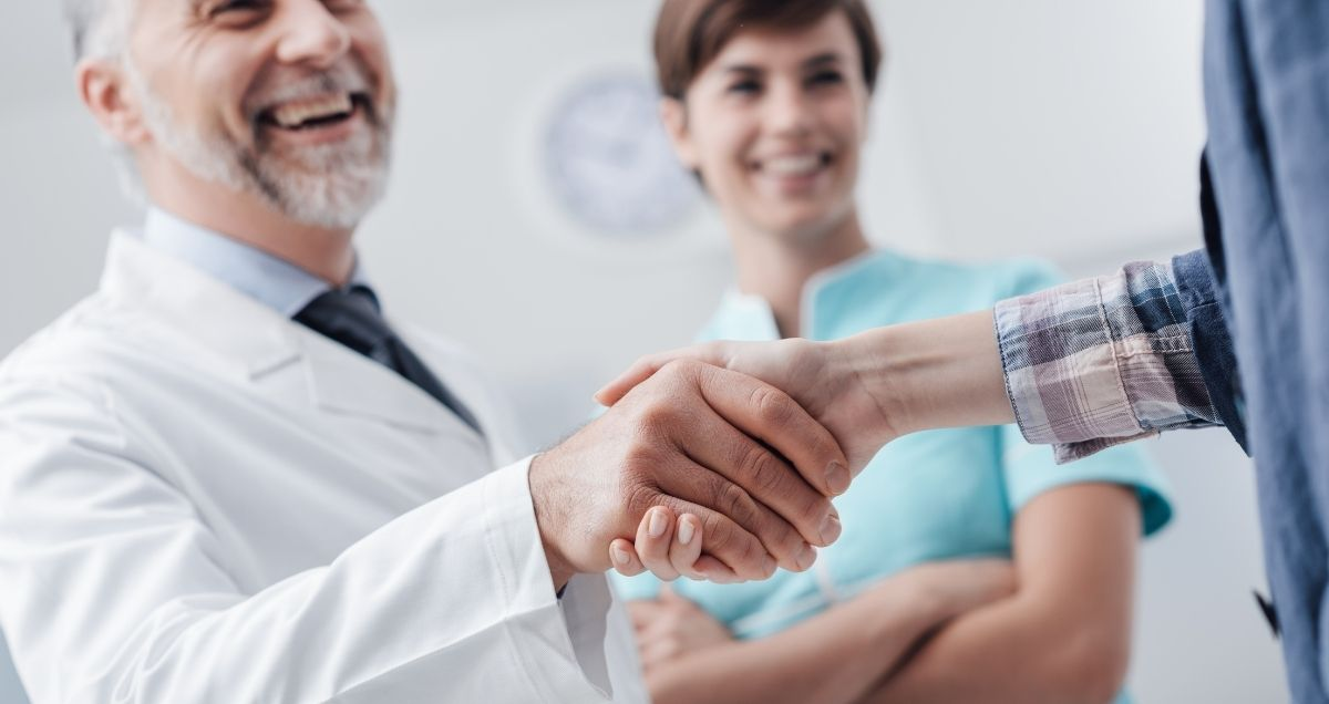 An elderly doctor shaking a patient's hand with a female nurse smiling in the background.