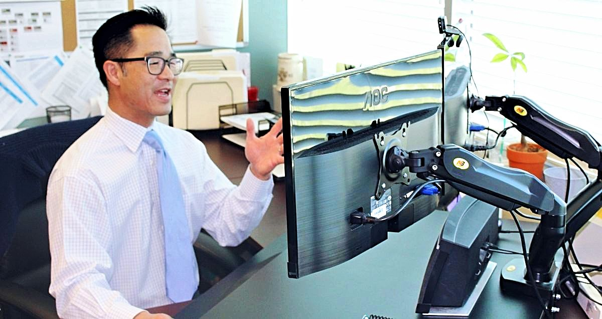 A talking doctor having a Telemedicine appointment on his computer at his desk.