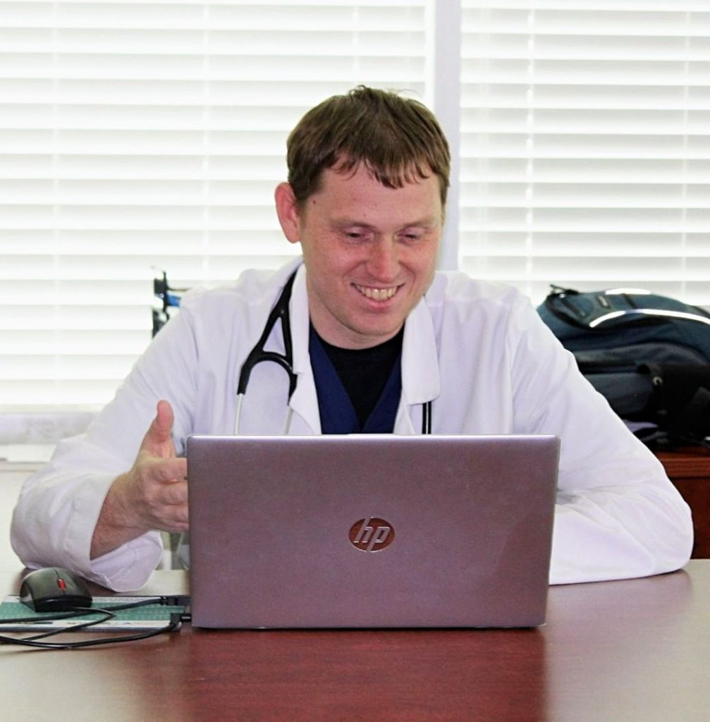 A smiling Physician Assistant with a stethoscope having a Telemedicine appointment on his laptop at his desk.
