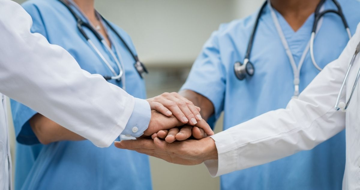 Four cooperative doctors in scrubs and lab coats huddled together in a circle with their hands together.