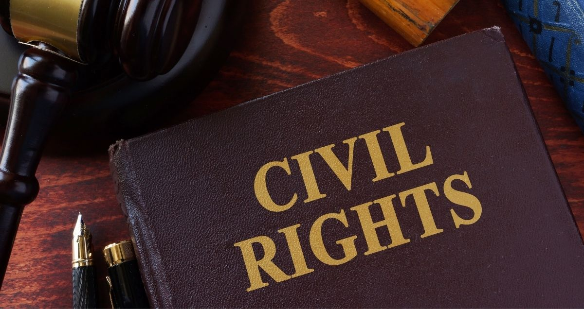 A civil rights book, gavel, and pen on a dark-wood desk.
