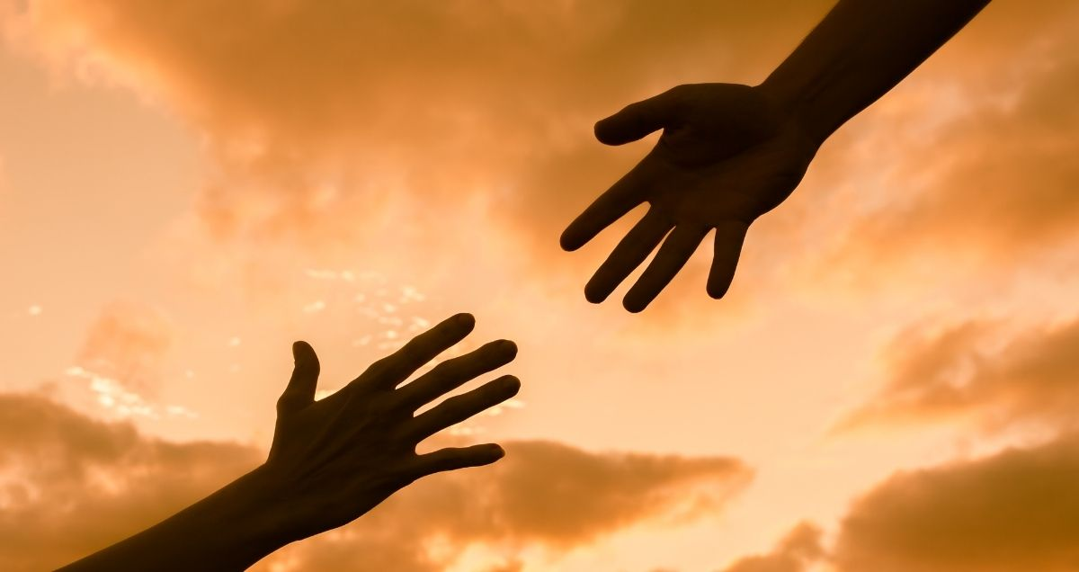 Two hands reaching out to each other in the orange sky filled with clouds.