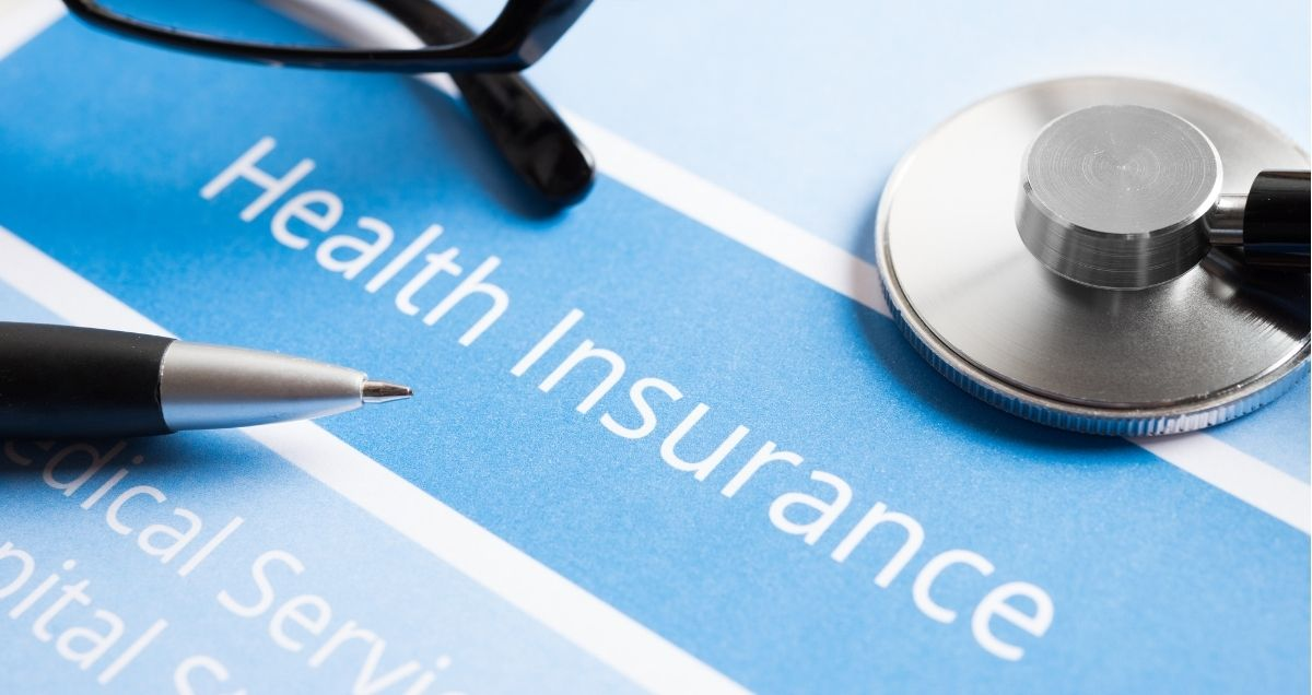 A pen, pair of glasses, and stethoscope are placed on top of a blue health insurance document.
