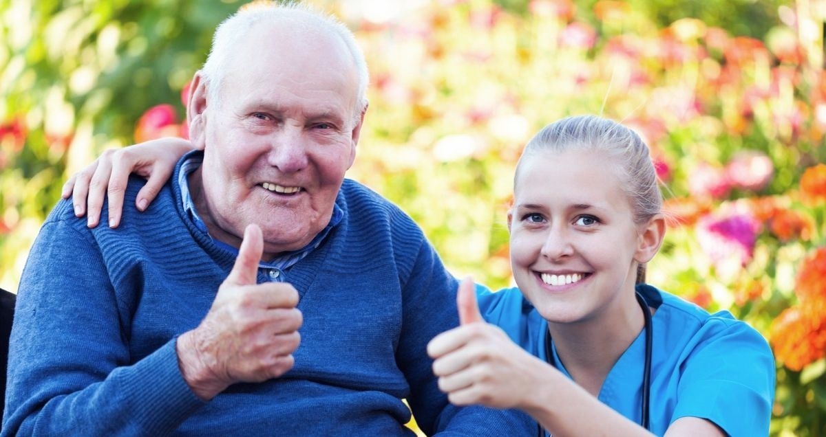 A smiling old man in a wheelchair and his kneeling nurse giving a thumbs up surrounded by tree leaves.