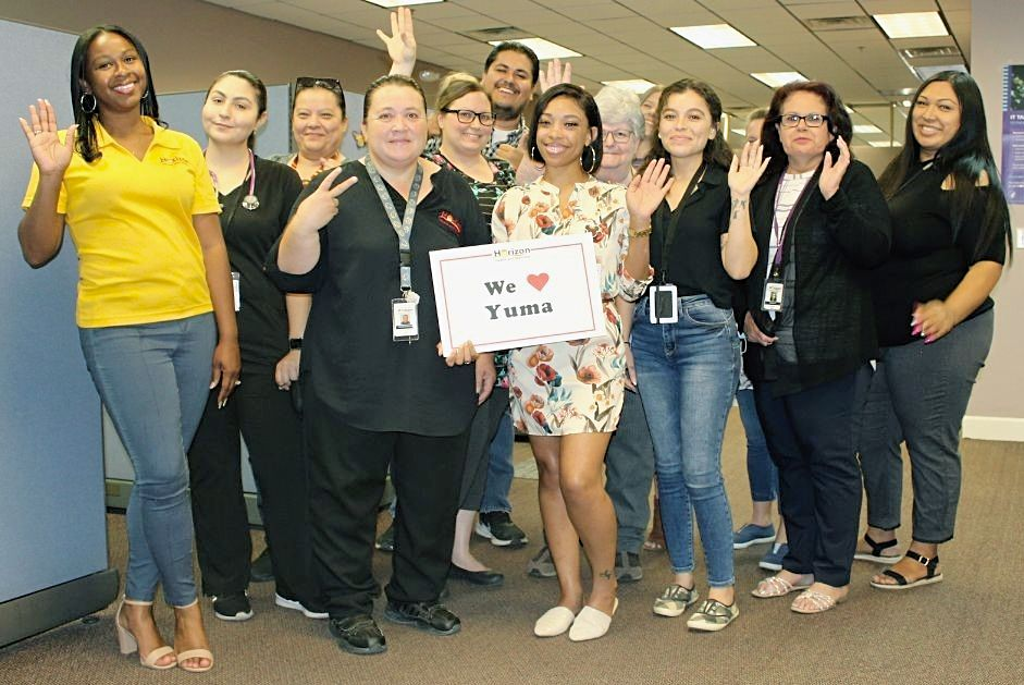 """The Horizon Health and Wellness staff at the Yuma Clinic holding a """"We love Yuma"""" sign."""