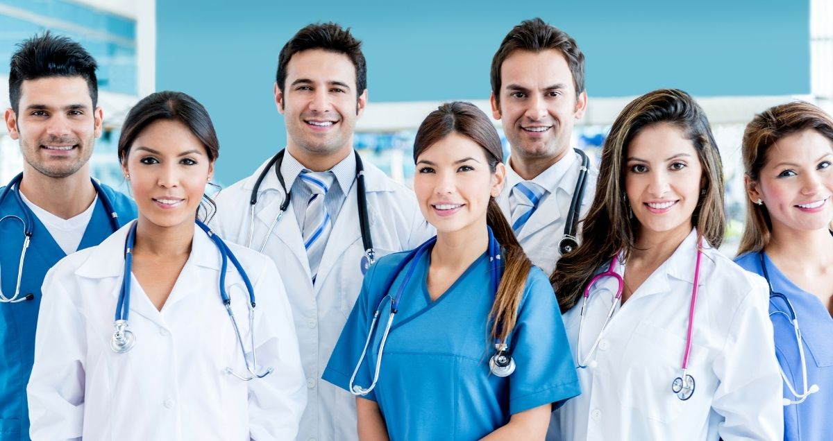 A diverse group of doctors and nurses wearing stethoscopes in a hospital setting.