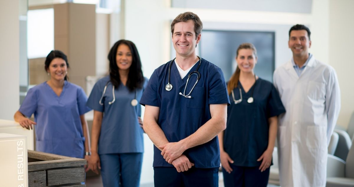 A middle-aged doctor standing in front of a diverse group of healthcare workers wearing scrubs and a lab coat.