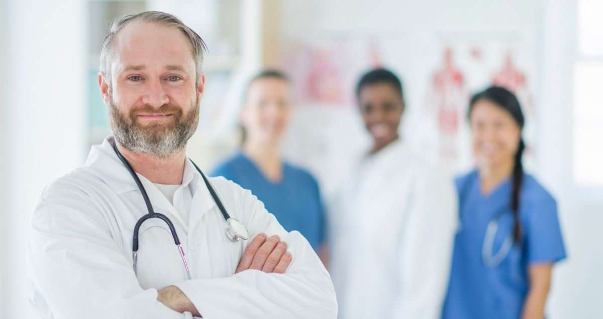 A caucasian, male doctor with a beard and arms crossed stands in front of female medical staff.