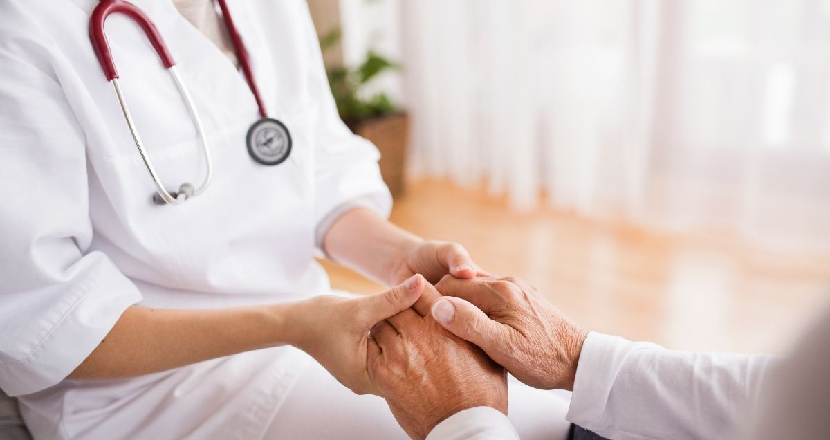 A compassionate nurse with a stethoscope holding a patient's hand.