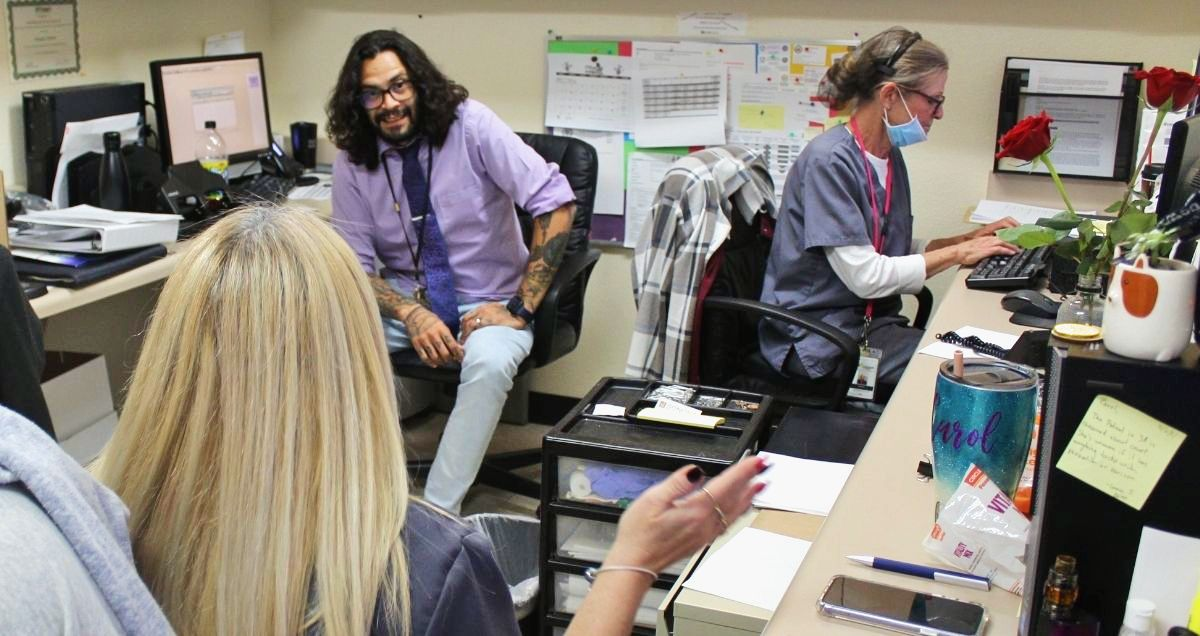 A diverse group of healthcare workers are talking to each other sitting at their desks.