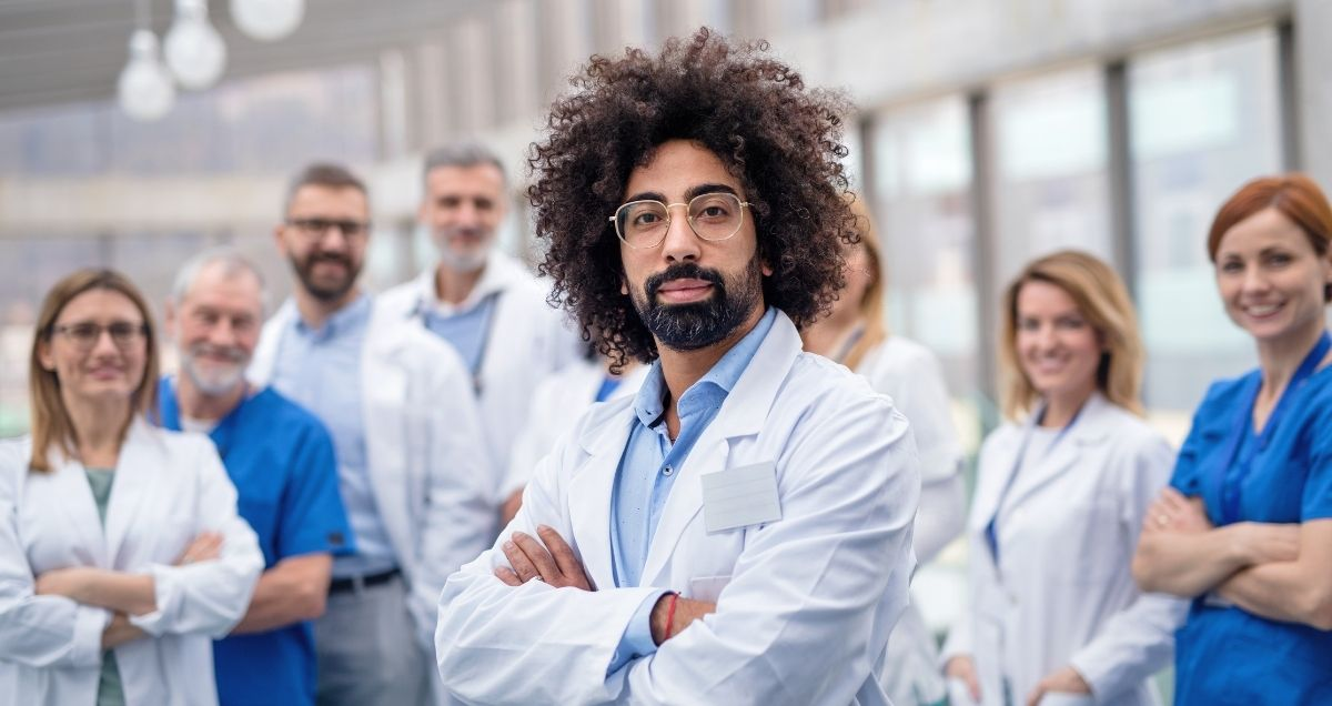 A confident African-American doctor wearing glasses standing in front of a group of medical staff.
