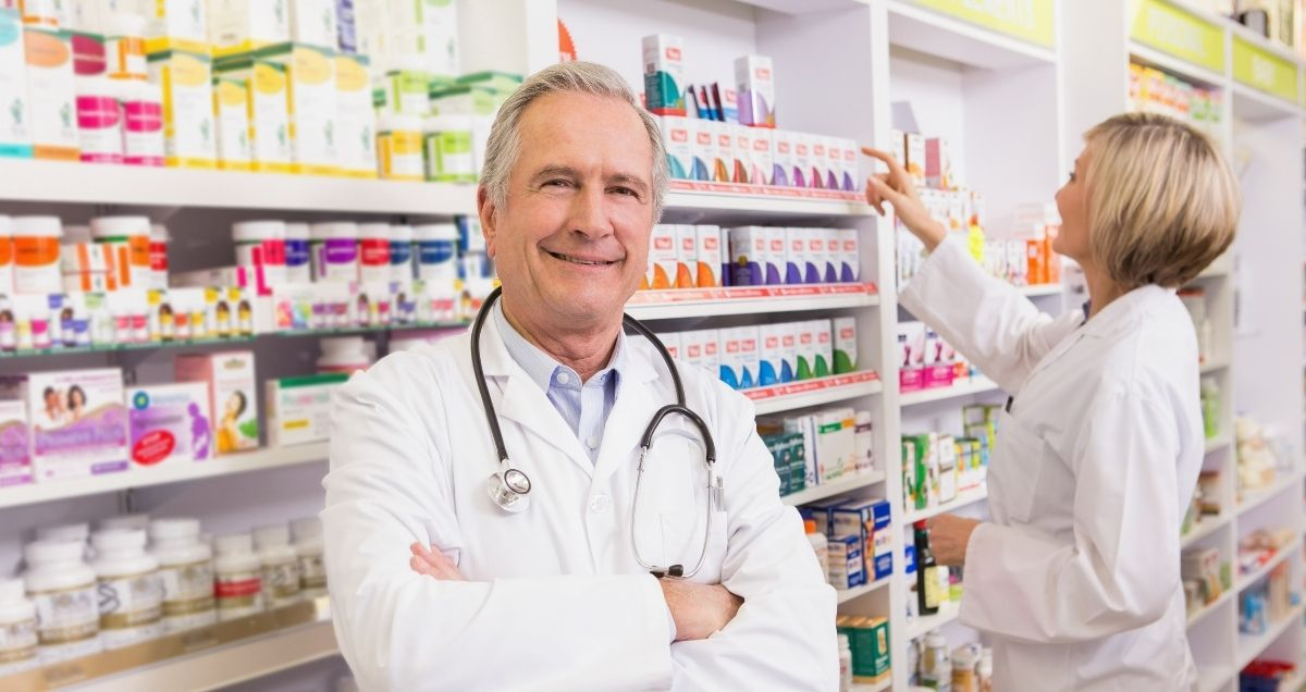 A pharmacist with arms crossed standing in front of shelves of medicine in a pharmacy.