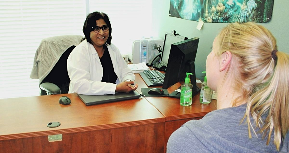 A Psychiatric-Mental Health Nurse Practitioner consulting and helping a patient at her desk.