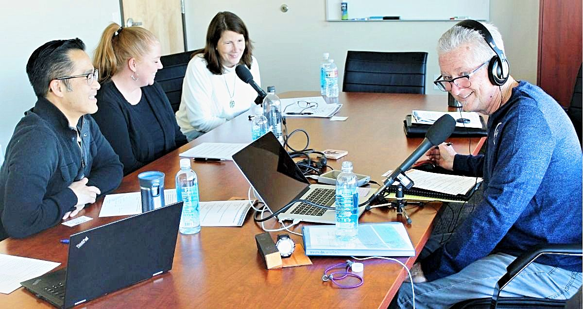 A radio interview in a conference room with three Horizon employees and the show host wearing headphones.