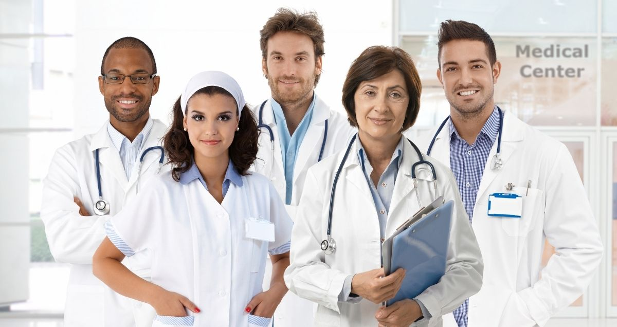 A diverse group of professional doctors and nurses in lab coats smiling with stethoscopes and clipboards.