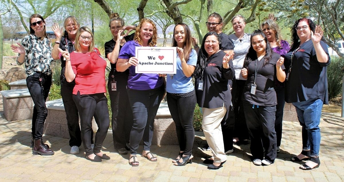 """The Horizon Health and Wellness staff at the Apache Junction holding a """"Apache Junction"""" sign."""