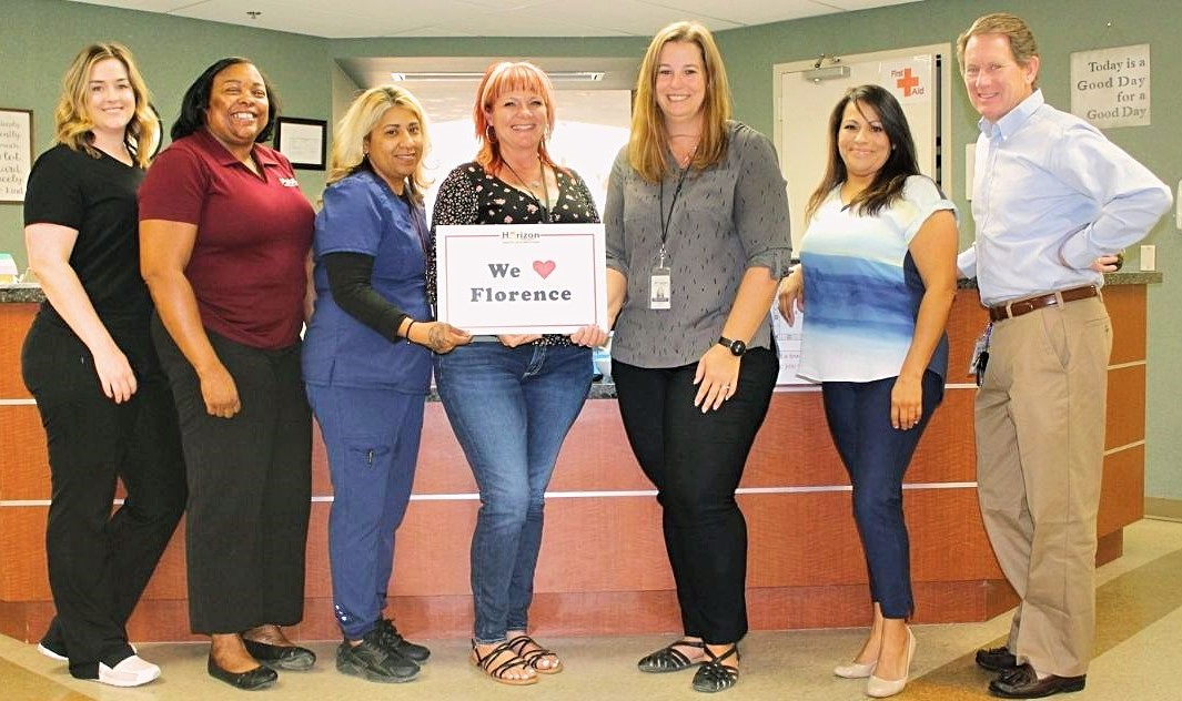 """The Horizon Health and Wellness staff at the Florence Clinic holding a """"We love Florence"""" sign."""