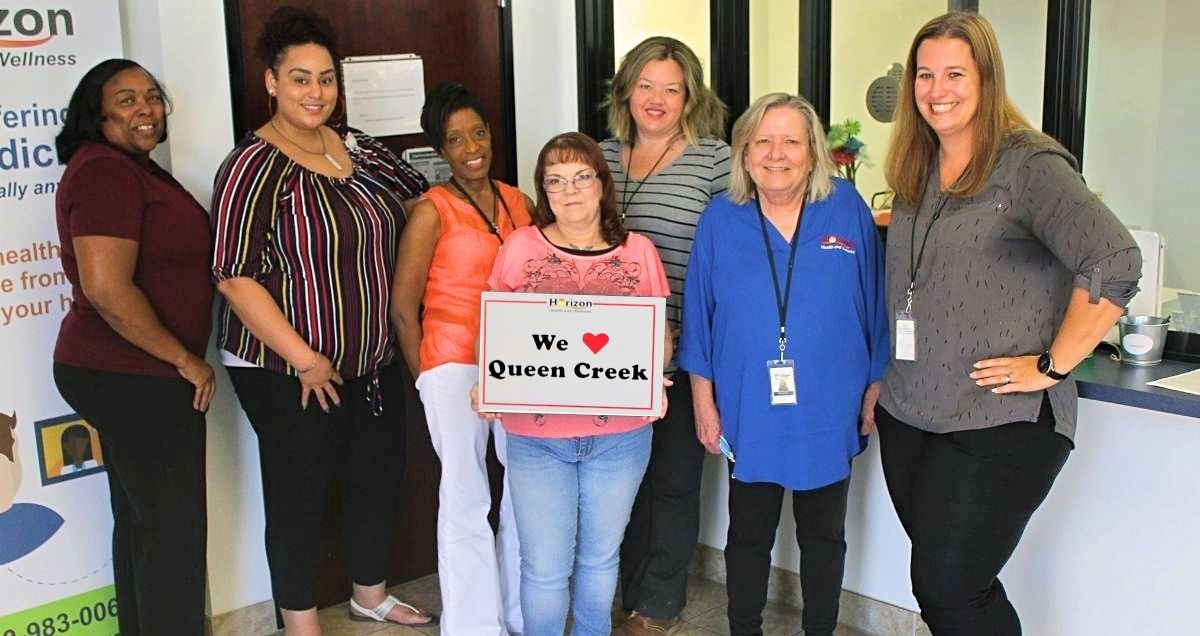 """The Horizon Health and Wellness staff at the Queen Creek Clinic holding a """"We love Queen Creek"""" sign."""