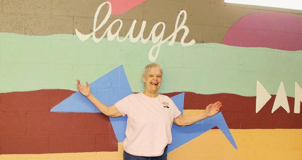 """A smiling disabled woman standing in front of a colorful wall with the word """"laugh"""" painted on it."""