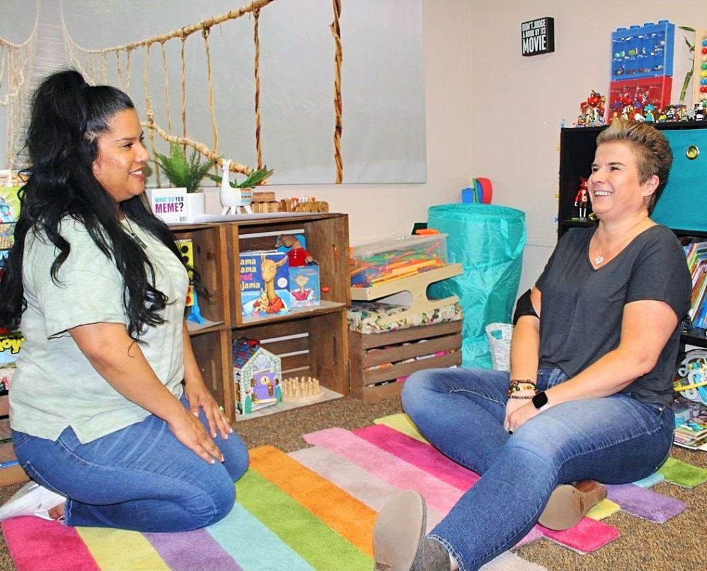 Laughing female Case Managers sitting on the floor in a children's play area surrounded by toys.