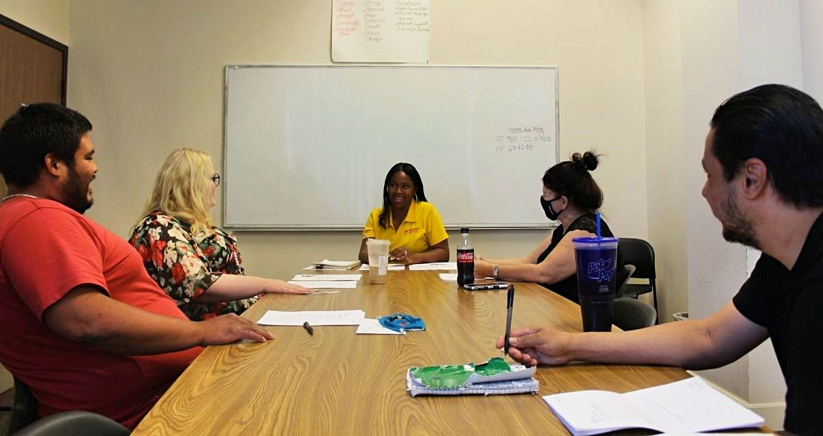 A substance abuse group therapy meeting with a female counselor in a conference room.