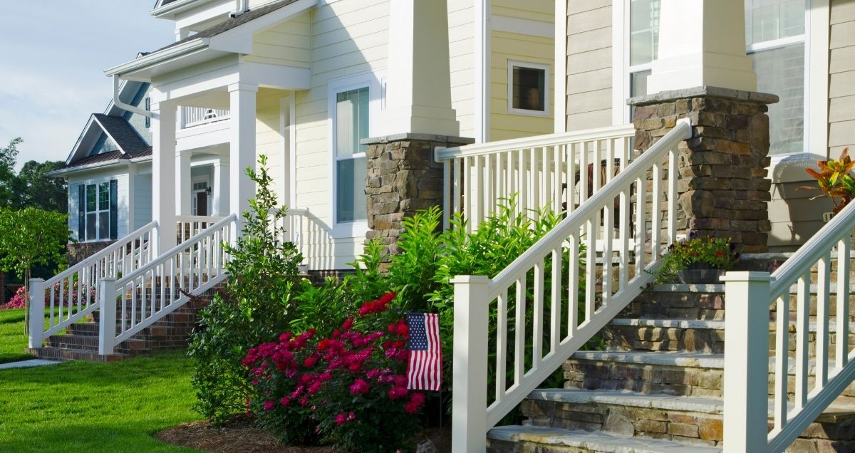 New and colorful townhomes with stairs leading to the front porch in a beautiful suburban neighborhood with front lawns.