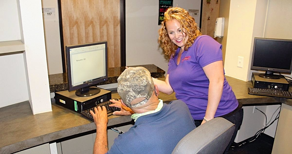 A smiling female employee helping a man type his resume on a computer in an office.